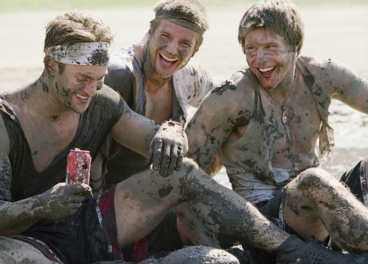 Close-up of three young men covered with mud smiling : Stock Photo