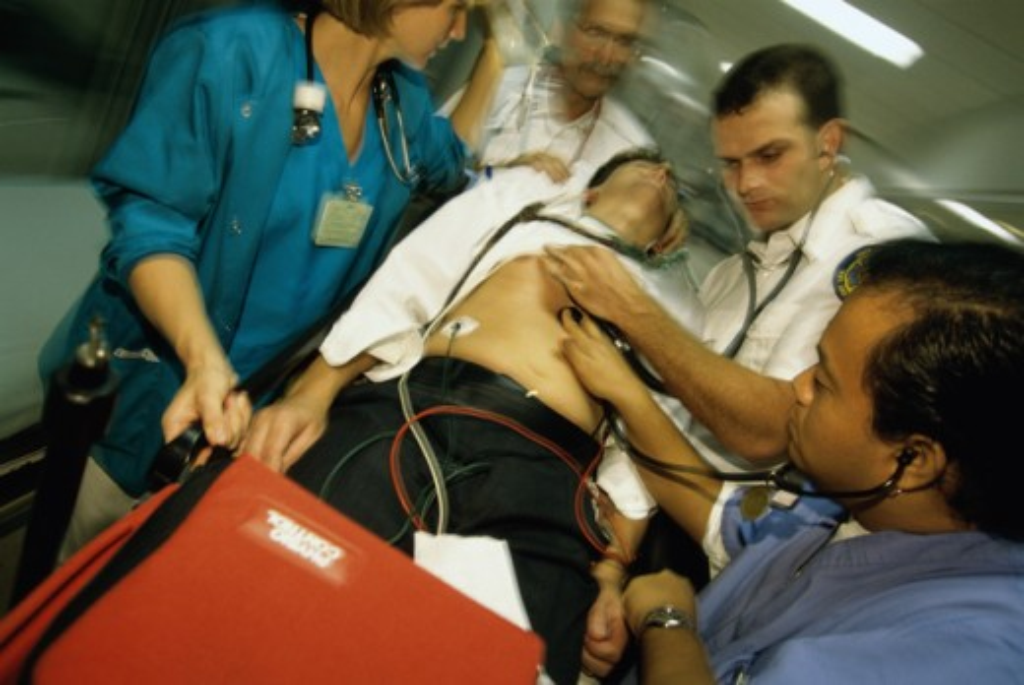 Paramedics pushing a man on a stretcher : Stock Photo