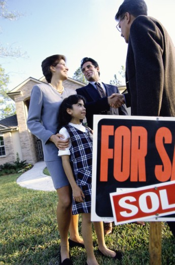 Parents and their daughter standing in front of a real estate agent : Stock Photo