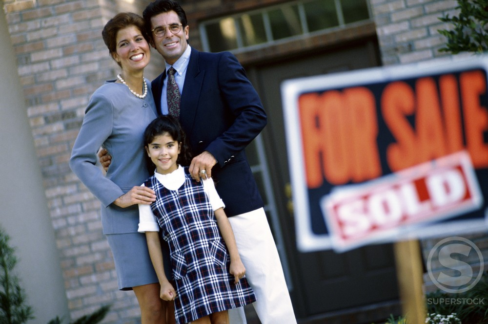 Stock Photo: 1097-414A Portrait of parents and their daughter standing in front of their new home