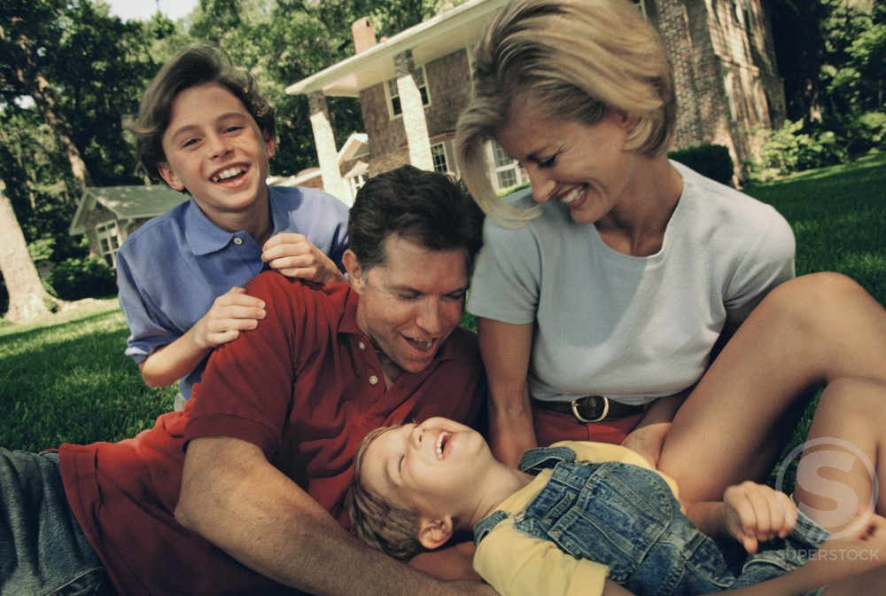 Stock Photo: 1098-1399 Mid adult couple with their two sons playing on a lawn