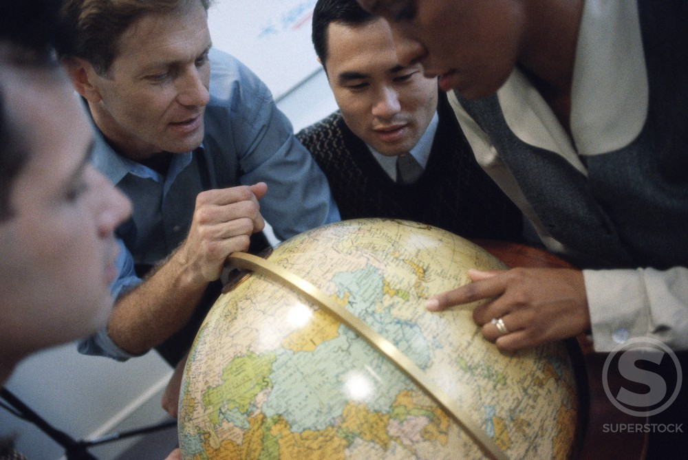 Stock Photo: 1098-213 Group of business executives looking at a globe