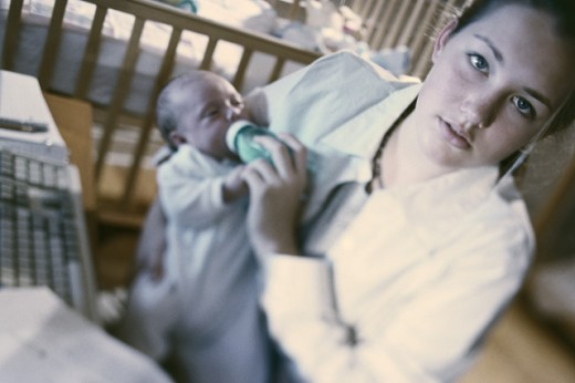 Portrait of a teenage mother feeding her baby girl : Stock Photo