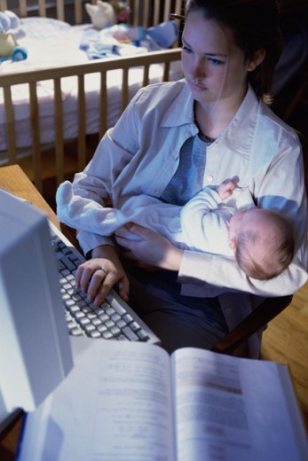 Stock Photo: 1098-2154 Teenage girl using a computer and carrying her baby girl