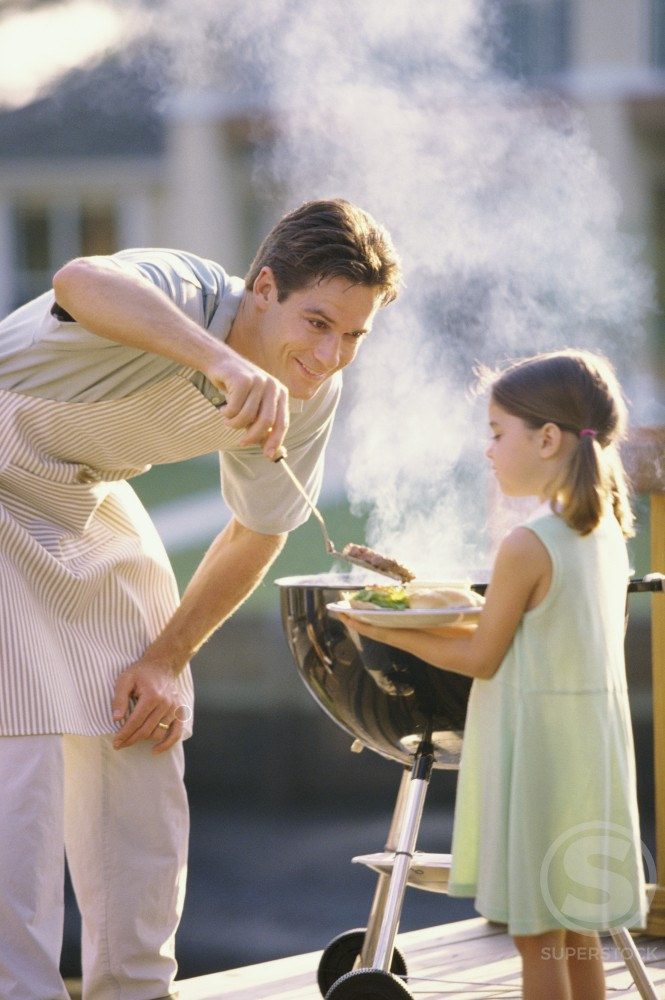 Father serving his daughter at a barbecue : Stock Photo