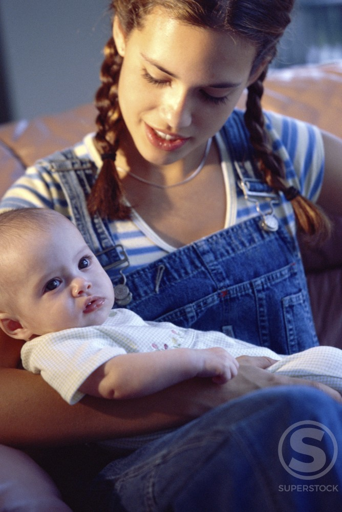 High angle view of a teenage girl holding her baby girl : Stock Photo