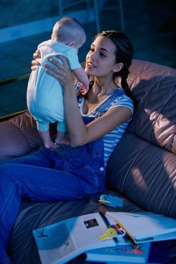 Teenage girl playing with her baby : Stock Photo