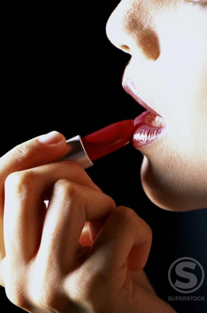 Young woman applying lipstick : Stock Photo