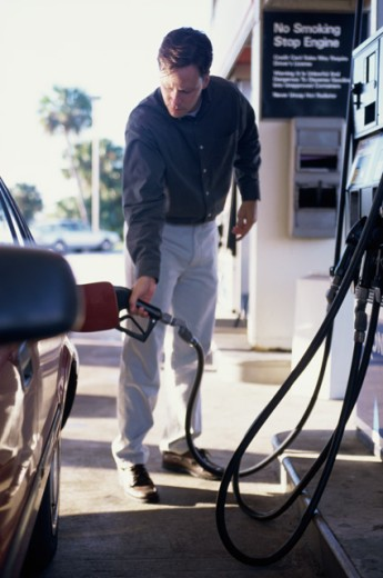 Young man refueling his car at a service station : Stock Photo