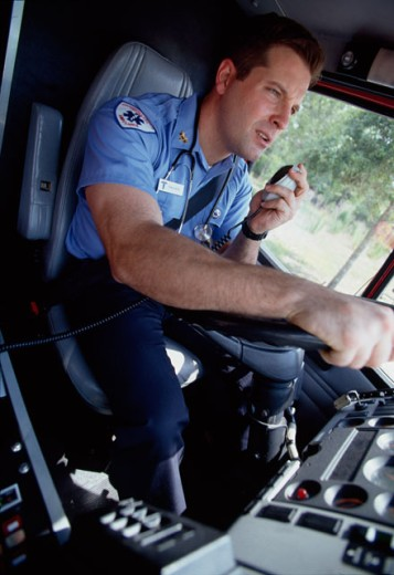 Stock Photo: 1098-4639A Emergency medical service worker driving an ambulance and talking on a CB radio