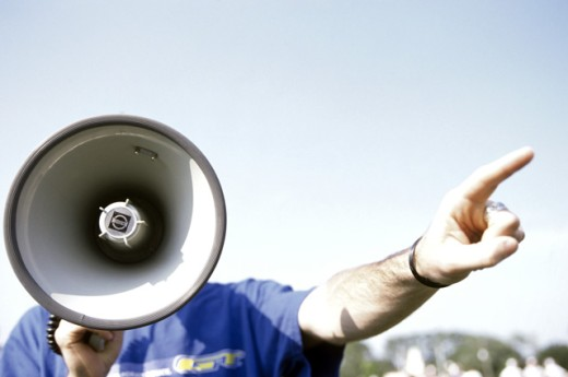 Man talking into a megaphone and pointing forward : Stock Photo