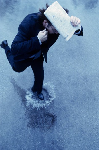 Stock Photo: 1098-6392A High angle view of a businessman running in the rain
