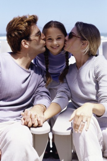Parents kissing their daughter : Stock Photo