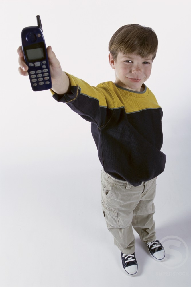 Portrait of a boy holding a mobile phone : Stock Photo