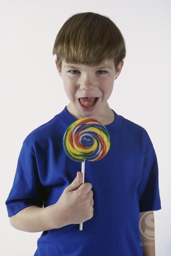 Portrait of a boy holding a lollipop : Stock Photo