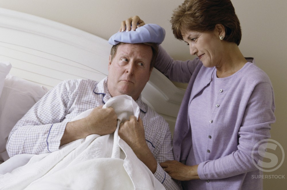 Stock Photo: 1098R-6129 Woman holding a cold pack on a man's head