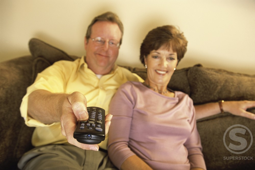 Mid adult couple sitting on a couch watching television : Stock Photo