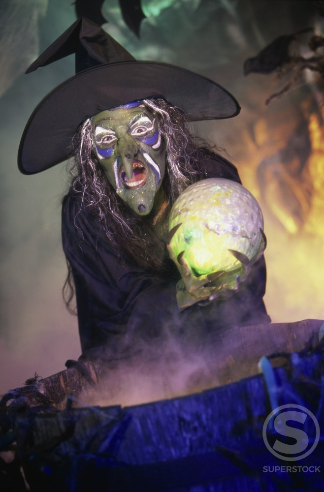 Witch holding a crystal ball standing in front of a cauldron : Stock Photo