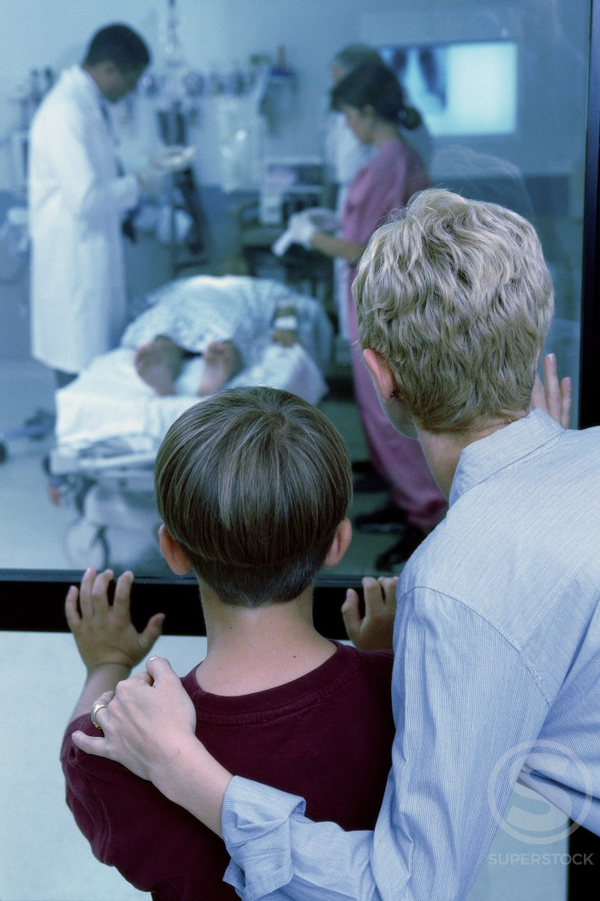 Stock Photo: 1099-1405 Rear view of mid adult woman standing with her son looking into an emergency room