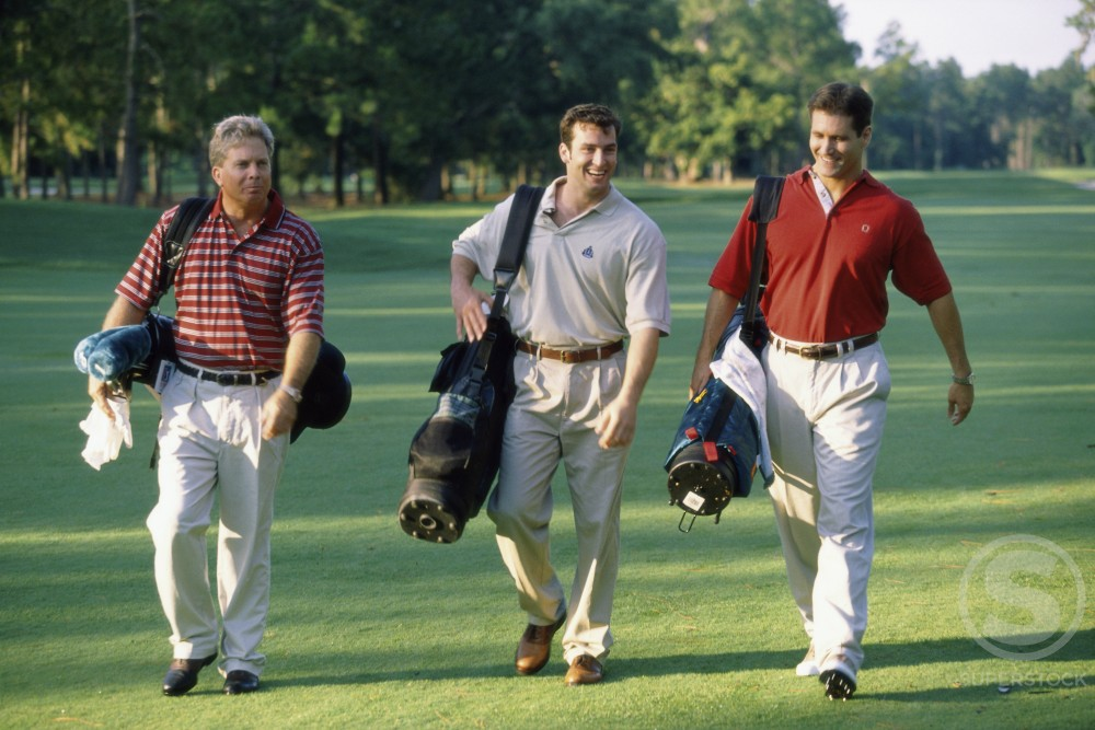 Three men walking on a golf course : Stock Photo