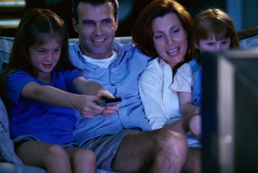 Parents watching television with their two daughters : Stock Photo