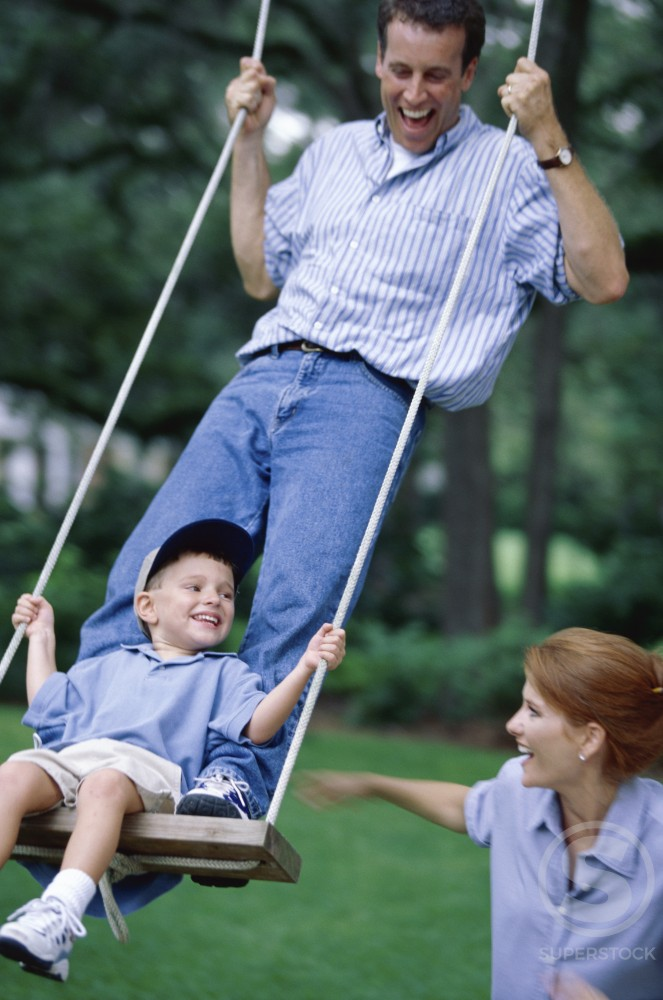 Stock Photo: 1099-2244 Father standing on a swing with his son