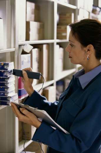 Mid adult woman checking the bar code on products in a warehouse : Stock Photo