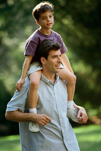 Stock Photo: 1099-2798 Mid adult man carrying his son on his shoulders