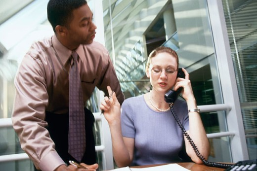 Stock Photo: 1099-3100 Businesswoman talking on the phone and a businessman standing behind her