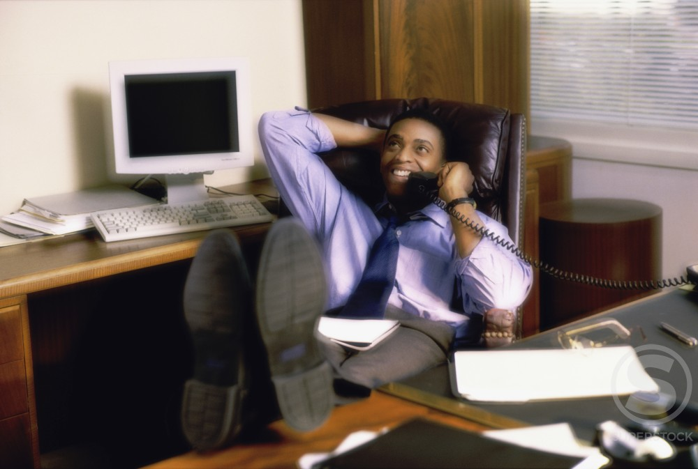 Stock Photo: 1099-3113A High angle view of a businessman sitting in an office talking on the telephone