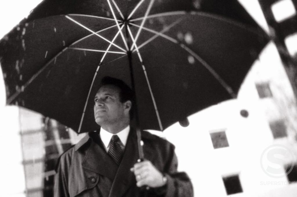 Businessman holding an umbrella : Stock Photo