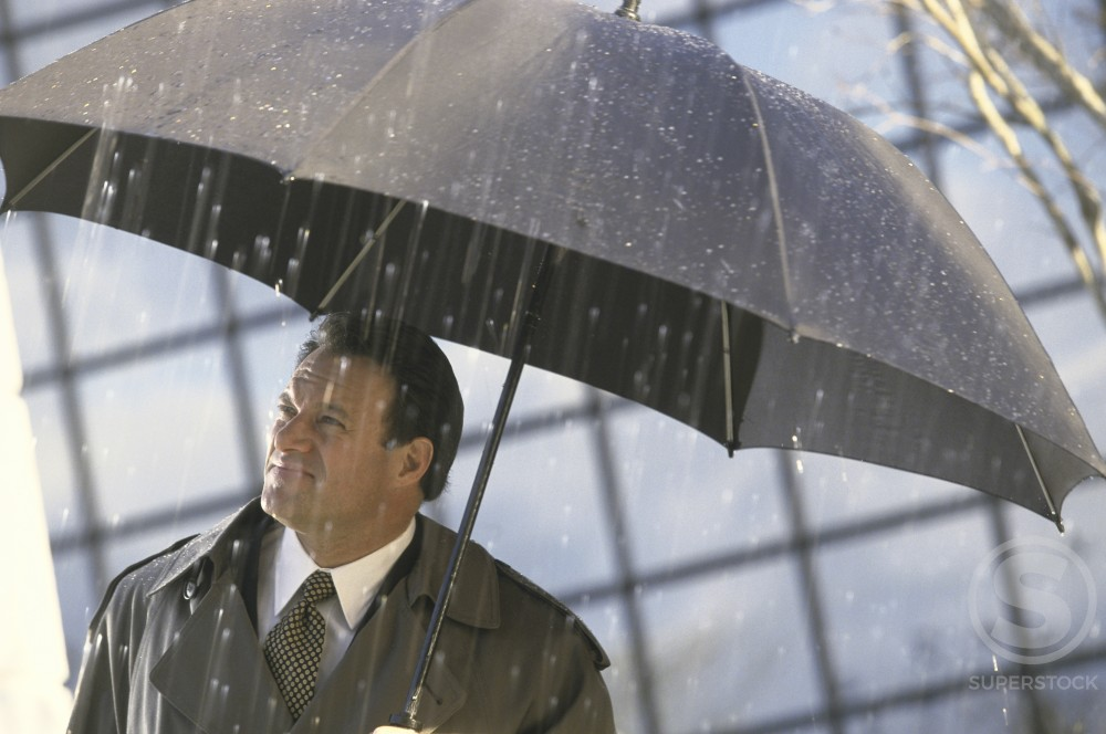 Stock Photo: 1099-3388A Businessman holding an umbrella