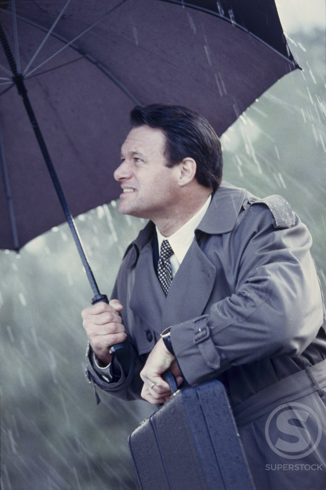 Stock Photo: 1099-3394A Businessman holding a briefcase and an umbrella in the rain