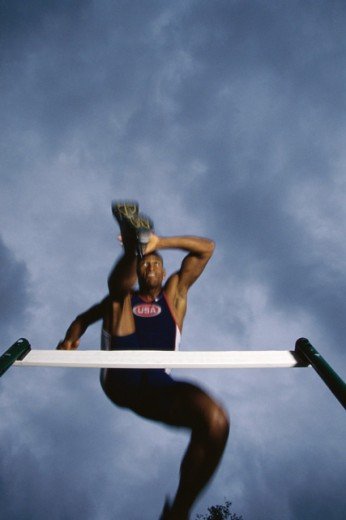 Low angle view of a young man jumping over a hurdle : Stock Photo