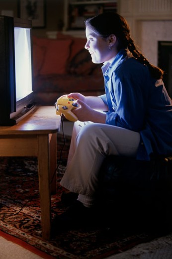 Stock Photo: 1099-4154B Side profile of a teenage girl playing a video game