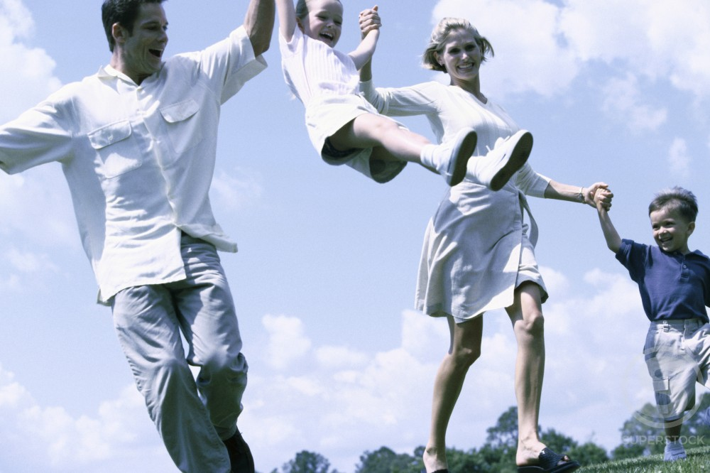Low angle view of parents swinging their daughter : Stock Photo