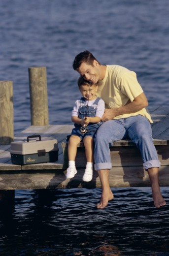 Stock Photo: 1099-4648A Father and his son sitting on a pier fishing