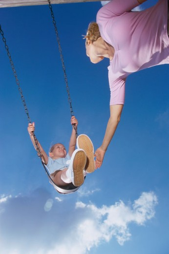 Stock Photo: 1099-4693N Low angle view of a mother pushing her daughter on a swing