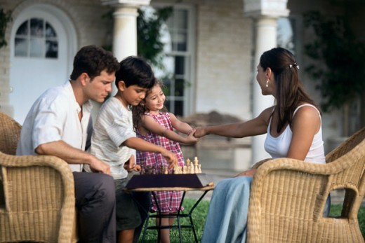 Side profile of a mid adult couple sitting in armchairs with their children playing chess : Stock Photo