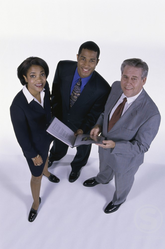 High angle view of a businesswoman and two businessmen smiling : Stock Photo