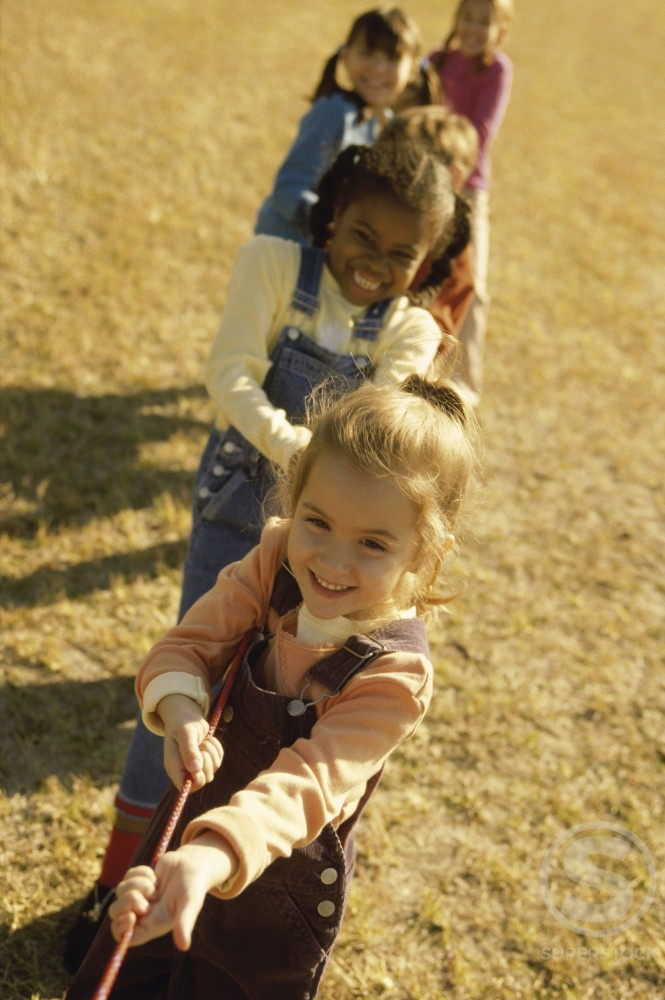Group of children playing tug-of-war : Stock Photo