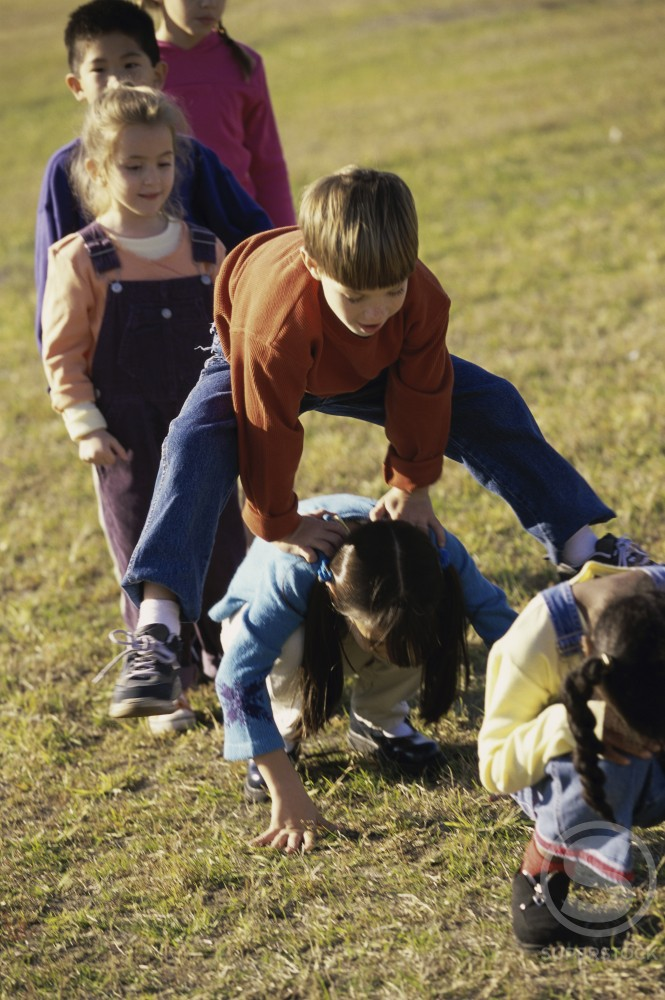 Stock Photo: 1099-5290 Group of children playing on a lawn