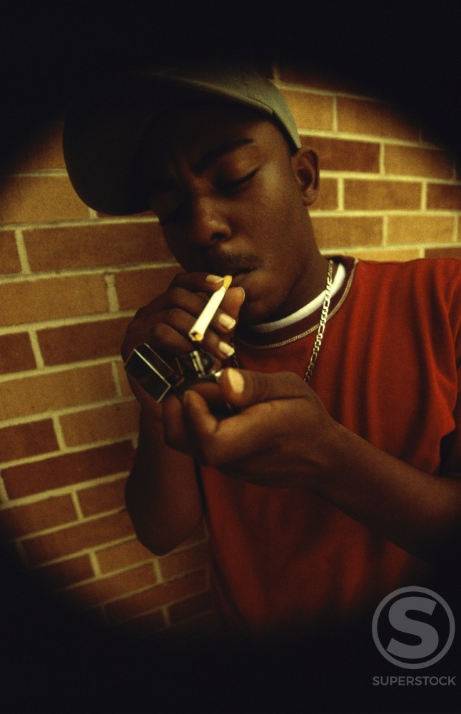 Stock Photo: 1099-5471A Teenage boy lighting a cigarette