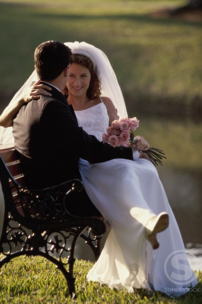 Stock Photo: 1099-5978C Newlywed couple sitting on a park bench