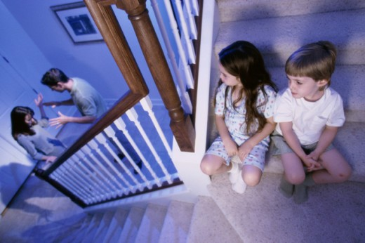 High angle view of a boy and a girl sitting on stairs while their parents fight : Stock Photo