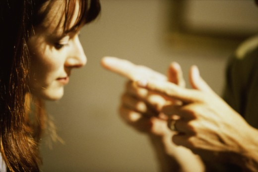 Young man pointing to a young woman : Stock Photo