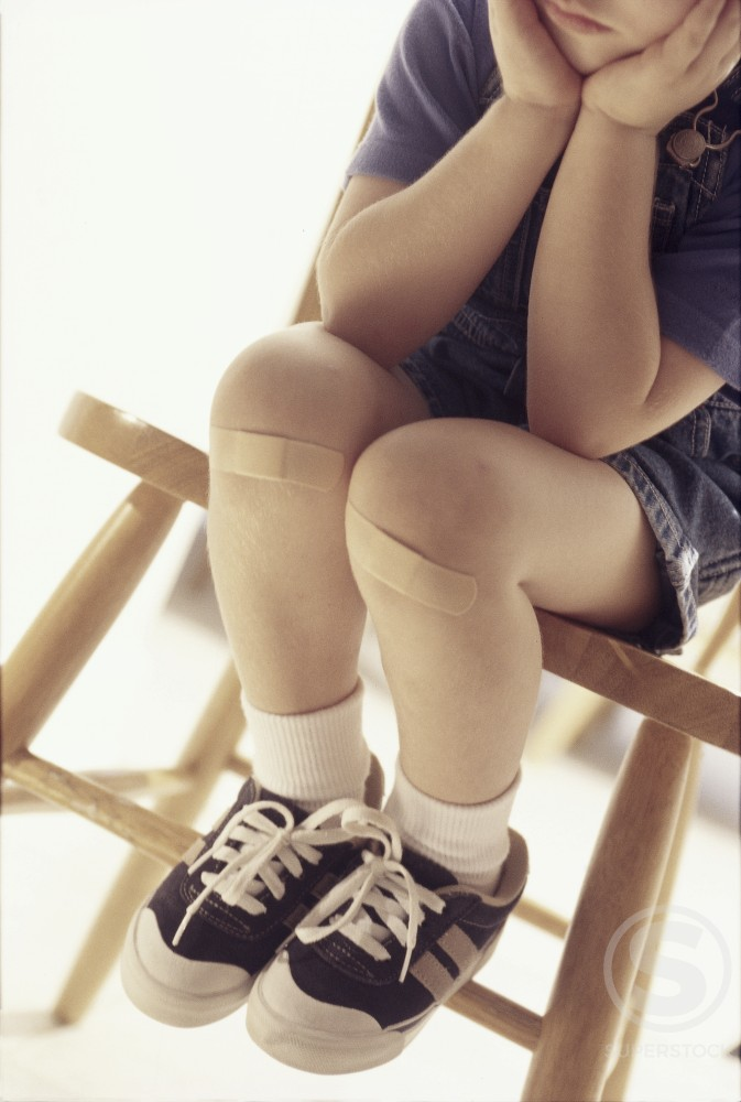 Stock Photo: 1099-6349 Low section view of a boy sitting on a chair