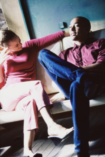 Stock Photo: 1099-6408 Young couple sitting together on a couch