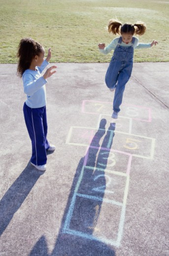 High angle view of two girls playing hopscotch : Stock Photo