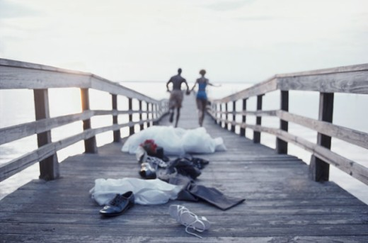 Rear view of a newlywed couple running on a pier : Stock Photo
